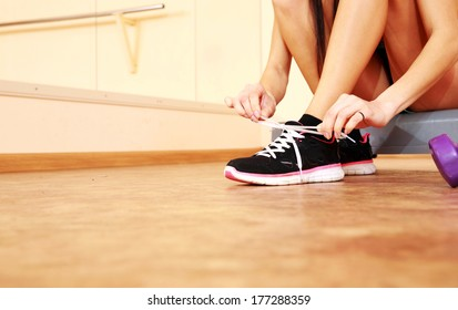 Young fit woman tying her shoelaces at gym