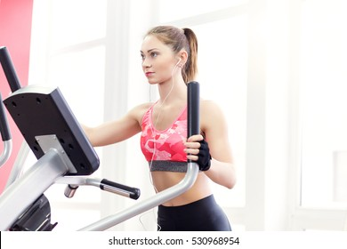 Young fit woman using an elliptic trainer in a fitness center, listening a music with headphones and smiling. Portrait of fitness girl in the gym near a window, lifestyle concept.