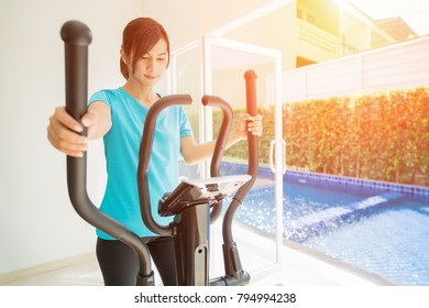 Young fit woman using an elliptic trainer in a fitness center,Portrait of fitness girl in the gym near a window, lifestyle concept.