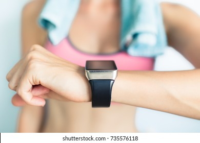 Young fit woman using smart watch at the gym.