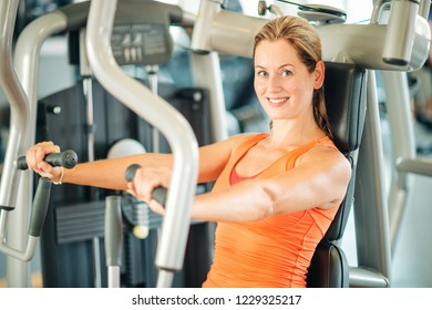Young fit woman working on a machine in gym