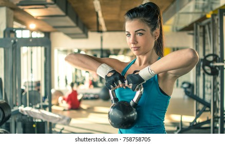Young fit woman working out with a kettle bell in the gym.
