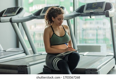 A young fit woman writes information in a training book for further progress in training in gym. Healthy lifestyle concept. Your workout plan
