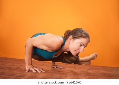 Young fit woman in yogasana posture over orange background