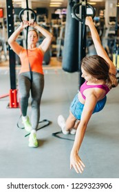 Young fit women doing stretching with trx fitness straps in the gym