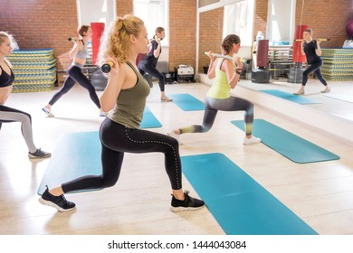 Young fit Women on a Yoga Pilates group class in gym. They stretch, stay in asana poses in sport outfit. Daylight. Indoors