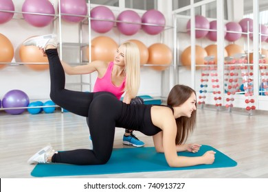 Young fitn and toned woman exercising with a personal trainer at the gym doing donkey kicks shaping her buttocks women body femininity shaping aerobics workout strengthening achieving concept.