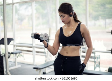 young fitness asian woman exercise with machine Cable Crossover and lifting dumbbells and barbells in gym for building muscles