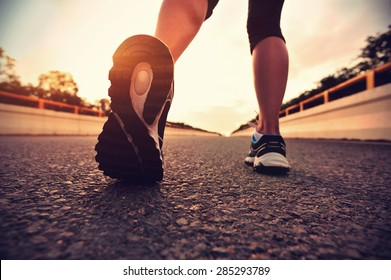 young fitness asian woman runner legs running on road