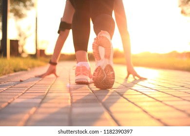 Young fitness attractive sporty girl runner in start position, closeup on shoe, outdoor at sunset or sunrise