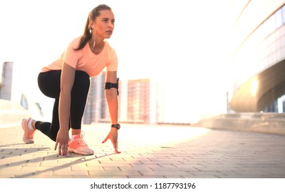 Young fitness attractive sporty girl runner in start position outdoor at sunset or sunrise in city.