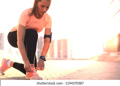 Young fitness attractive sporty girl runner ties up the shoelaces on her sports shoes getting ready to run.