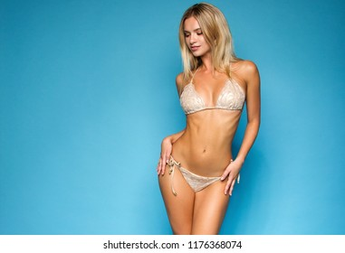 young fitness blonde girl in beige swimsuit is standing sexy and flirting like model on the blue wall background