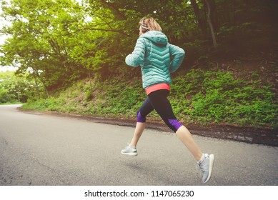 Young fitness blonde woman in headphones running at morning caucasian forest trail in sun light. side view from behind