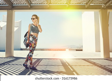 Young fitness blonde woman in sportswear listening music with headphones after training outdoors at beautiful sunny day. Girl runner enjoying sun and listen music in earphones from smartphone.