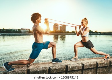 Young fitness couple is doing workout with rubber band by the river in a sunset.