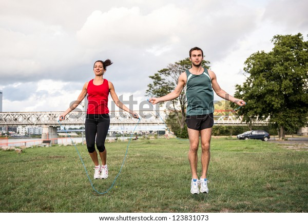 Young fitness couple exercising outdoor - jumping with skipping rope