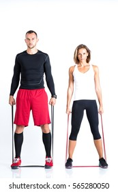 Young fitness couple training with resistance bands isolated on white. Sports and fitness concept