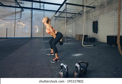Young fitness female exercise with kettle bell. Caucasian woman doing crossfit workout at gym.