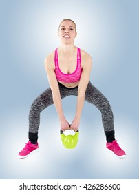 Young fitness female exercise with kettle bell. Mixed race woman doing crossfit workout on grey background. Kettlebell swing.
