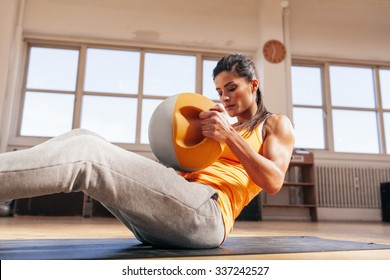 Young fitness female exercising with kettle bell. Muscular young woman in sportswear doing crossfit workout in gym.