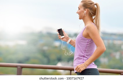 Young fitness female joger is runing and listening to music during the run in city on a quay. Healthy wellness fitness lifestyle