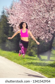 Young fitness female running and jumping outdoor
