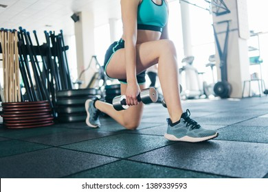 Young fitness girl doing lunges for legs with dumbbells in her hands close up in gym.