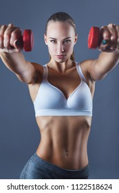 Young fitness girl with dumbbells against a grey background