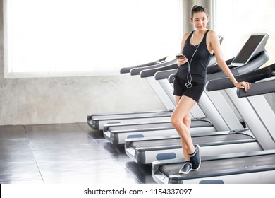 Young fitness girl in sport wear relaxing and listening to music with smartphone on the treadmill in the gym, Exercise working out with earphones with copy space.runnig machine