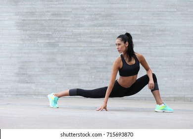 young fitness girl with a sports figure doing stretching