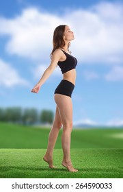 Young fitness girl standing  on green grass .