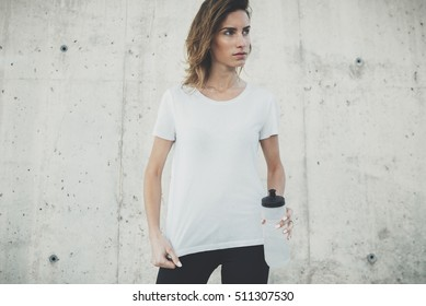 Young fitness girl wearing blank white t-shirt with empty area for design or text message, mock-up of template white t-shirt, female jogger after active workout outside, concrete wall in background