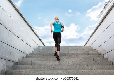Young fitness healthy woman runner running on city stairs