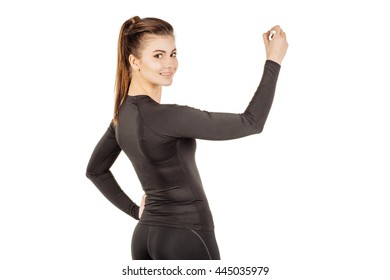 young fitness instructor from the back wearing sportswear writing something in the air with marker . isolated on white background. fitness, sport and health concept.