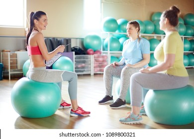Young fitness instructor and her group sitting on green fitballs in gym and discussing which exercises they are going to do