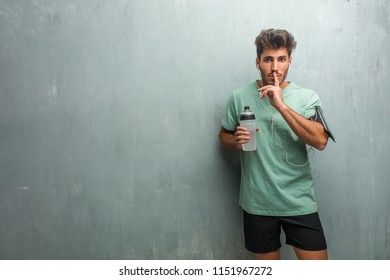 Young fitness man against a grunge wall keeping a secret or asking for silence, serious face, obedience concept. Wearing an armband with phone.