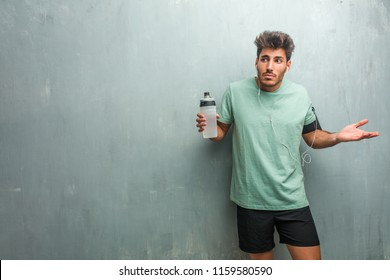Young fitness man against a grunge wall doubting and shrugging shoulders, concept of indecision and insecurity, uncertain about something. Wearing an armband with phone.