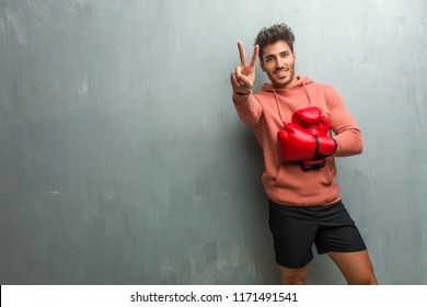 Young fitness man against a grunge wall showing number two, symbol of counting, concept of mathematics, confident and cheerful.