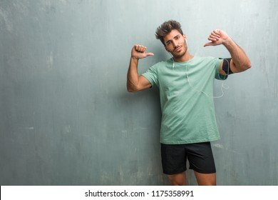 Young fitness man against a grunge wall proud and confident, pointing fingers, example to follow, concept of satisfaction, arrogance and health. Wearing an armband with phone.