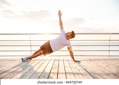 Young fitness man doing yoga exercise outdoors at the beach pier