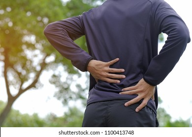 Young fitness man holding his sports  injury, muscle painful during training. Asian runner having back flank ache and problem after running and exercise outside in summer