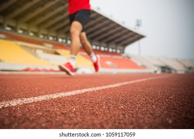 young fitness man run on athlete running track