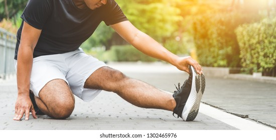 Young fitness man runner stretching before run with copy space healthy lifestyle and sport concepts