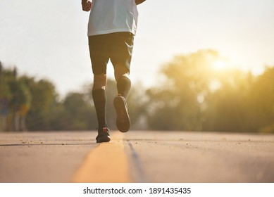 Young fitness man running at road with sunrise background