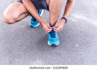 Young fitness man tying running shoes on street, blur background