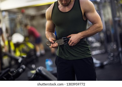 Young fitness man wearing leather gym protection belt.