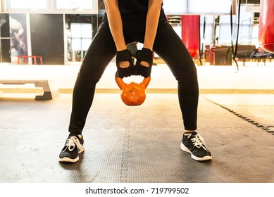 Young fitness model doing a kettle bell exercise in the gym.