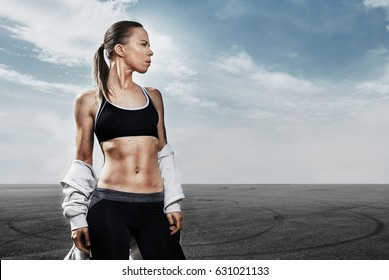 Young fitness model girl looks to the right on blue sky background