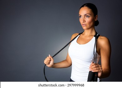 Young fitness model posing with jump rope against dark grey background.